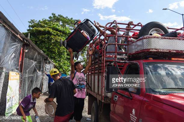 Honduran migrants board a truck as they take part in a caravan heading to the US near Huehuetan on their way from Tapachula to Huixtla Chiapas state...