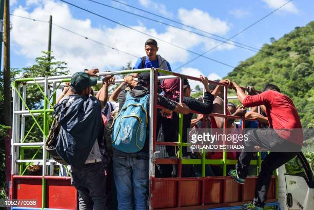 Honduran migrants board a truck as they take part in a new caravan heading to the US in Quezaltepeque Chiquimula Guatemala on October 22 2018 US...