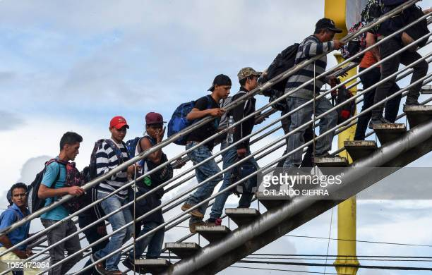 TOPSHOT Honduran migrants climb an overpass to go to Tecum Uman Guatemalan border with Mexico in Guatemala City on October 18 2018 US President...