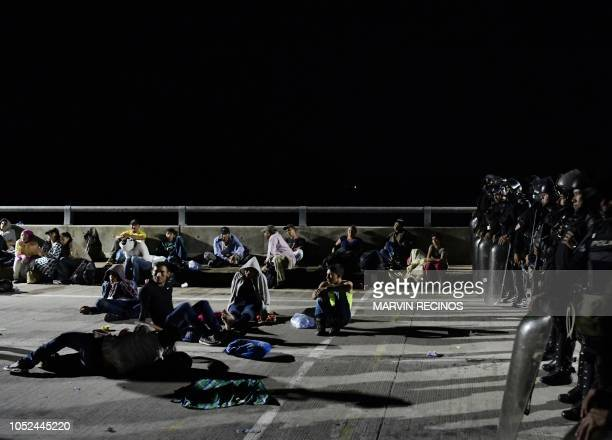 TOPSHOT Honduran migrants heading for the US rest next to a line of riot police in El Amatillo La Union department El Salvador in the border with...