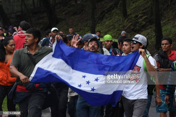 Honduran migrants heading in a caravan to the United States walk with a Honduran national flag in direction to Tecun Uman the border with Mexico as...