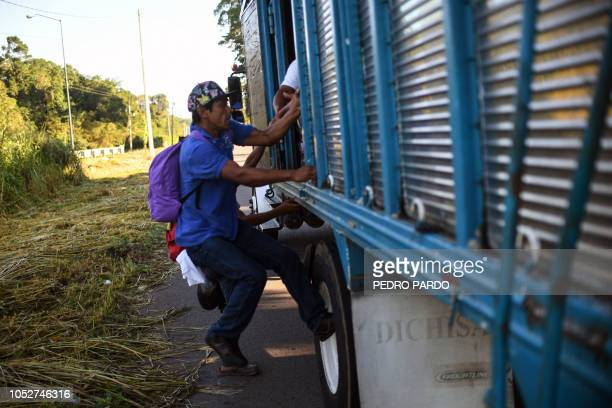 Honduran migrants heading in a caravan to the US board a truck in Metapa on their way to Tapachula Chiapas state Mexico on October 22 2018 President...