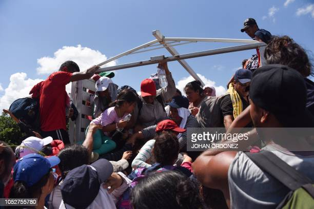 Honduran migrants heading in a caravan to the US climb on a truck in Tapachula Chiapas state Mexico on October 22 2018 President Donald Trump on...