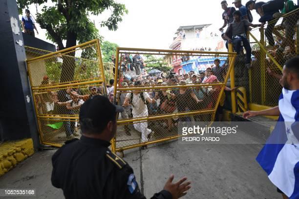 TOPSHOT Honduran migrants heading in a caravan to the US push to tear down the gate of the GuatemalaMexico international border bridge in Ciudad...