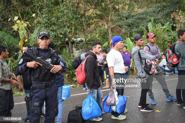 Honduran migrants heading to the United States with a second caravan wait next to police in Agua Caliente Chiquimula region Guatemala on the...