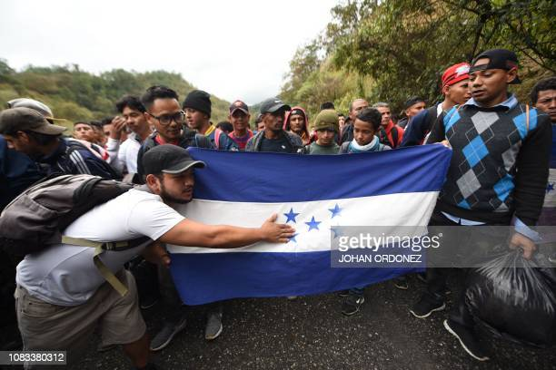 Honduran migrants holding a Honduran flag continue to head to the United States with a second caravan after reaching an agreement with the Guatemalan...