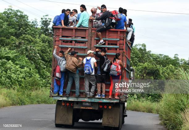 Honduran migrants onboard a truck in direction to Tecun Uman in the border with Mexico take part in a caravan heading to the US in Coatepeque...