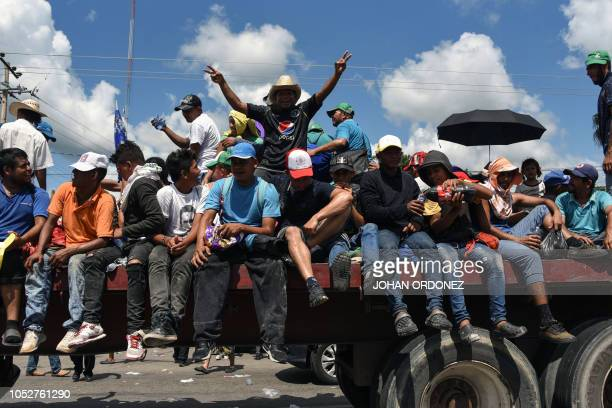 Honduran migrants onboard a truck take part in a caravan heading to the US in the outskirts of Tapachula on their way to Huixtla Chiapas state Mexico...