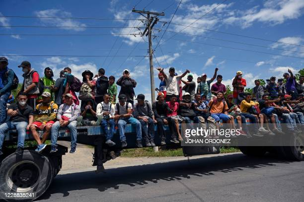 Honduran migrants, part of a caravan heading to the US, are seen onboard a truck in Entre Rios, Guatemala, after crossing the border from Honduras,...