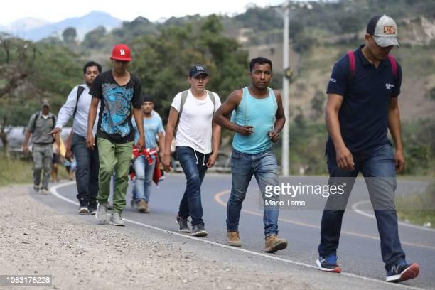 """Honduran migrants, part of a new """"migrant caravan,"""" walk as they make their way toward Guatemala on January 15, 2019 near Santa Rosa de Copan,..."""
