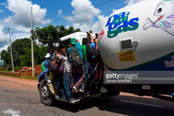 Honduran migrants standing on the running board of a truck take part in a caravan heading to the US in the outskirts of Tapachula on their way to...
