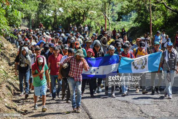 TOPSHOT Honduran migrants take part in a new caravan heading to the US with Honduran and Guatemalan national flags in Quezaltepeque Chiquimula...