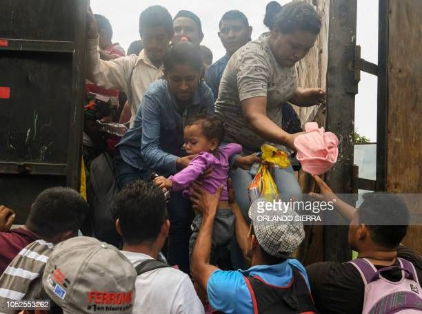 Honduran migrants taking part in a caravan heading to the US aboard a truck arrive at the border crossing point with Mexico in Ciudad Tecun Uman...