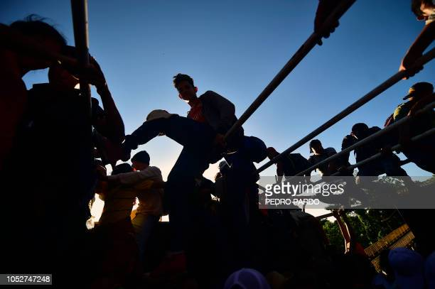 Honduran migrants taking part in a caravan heading to the US aboard a truck in Metapa on their way to Tapachula Chiapas state Mexico on October 22...