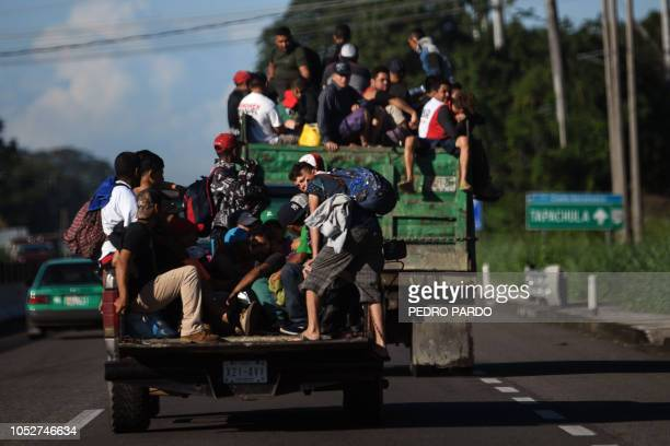 Honduran migrants taking part in a caravan heading to the US aboard trucks in Metapa on their way to Tapachula Chiapas state Mexico on October 22...