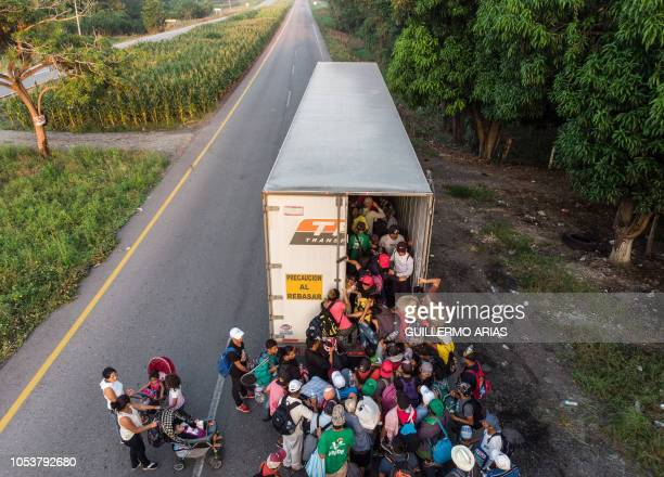Honduran migrants taking part in a caravan heading to the US get on a truck near Pijijiapan southern Mexico on October 26 2018 The Pentagon is...