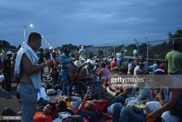 Honduran migrants taking part in a caravan heading to the US rest as they arrive at the border crossing point with Mexico in Ciudad Tecun Uman...