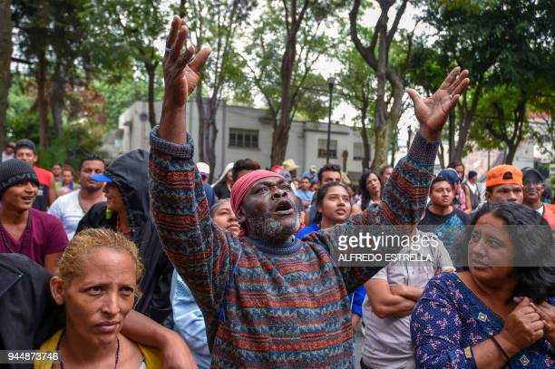 Honduran migrants taking part in the 'Migrant Via Crucis' caravan protest outside Honduras embassy in Mexico City on April 11 2018 The caravan an...