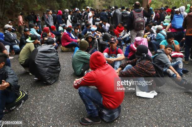 Honduran migrants who are part of a new 'migrant caravan' sit as police block a roadway to a border checkpoint into Guatemala on January 16 2019 in...