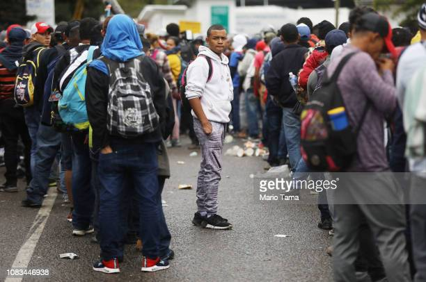 Honduran migrants who are part of a new 'migrant caravan' wait in long lines to try to officially cross over the border checkpoint into Guatemala on...