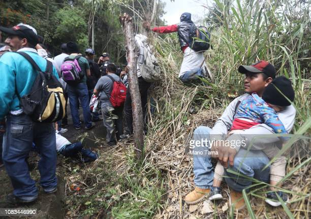 Honduran migrants who are part of a new 'migrant caravan' wait in the grass as police block a roadway to a border checkpoint into Guatemala on...
