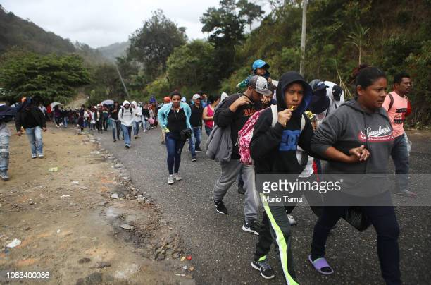 Honduran migrants who are part of a new 'migrant caravan' walk on a roadway to a border checkpoint into Guatemala on January 16 2019 in Agua Caliente...