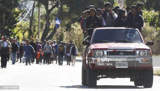 Honduran migrants who are part of a new 'migrant caravan' walk on a roadway to a border checkpoint as farm workers not in the caravan ride by on...