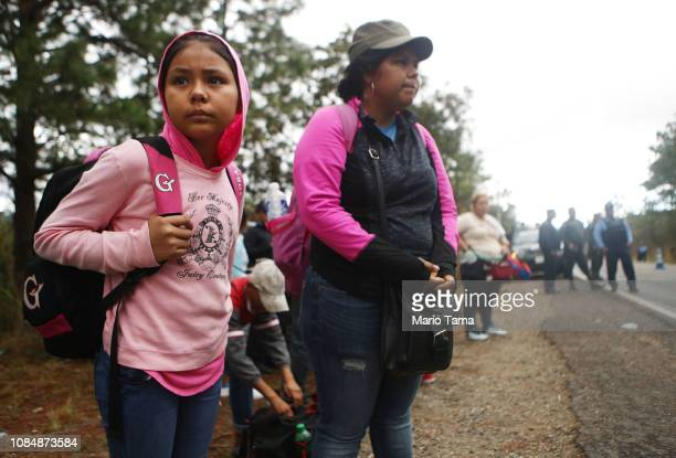 Honduran mother and daughter who were part of a new 'migrant caravan' stand by the side of a road after being pulled off their bus at a police...