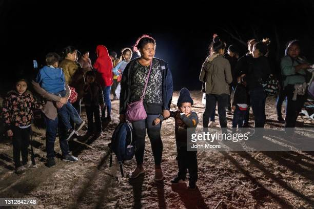 Honduran mother and son stand on the bank of the Rio Grande after rafting across the border from Mexico on April 14, 2021 in Roma, Texas. A surge of...