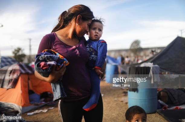 Honduran mother holds her son at a temporary shelter for members of the 'migrant caravan' located within sight of the USMexico border barrier on...