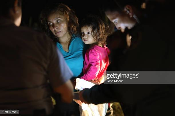Honduran mother holds her twoyearold as US Border Patrol as agents review their papers near the USMexico border on June 12 2018 in McAllen Texas The...