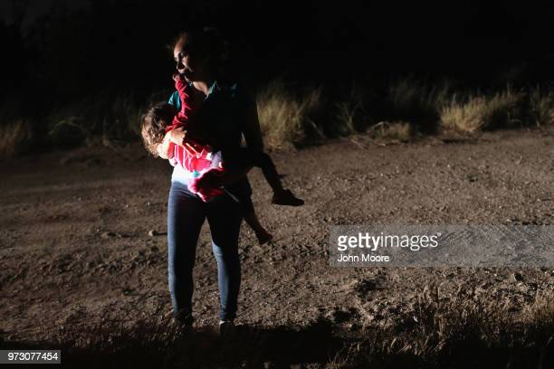 Honduran mother holds her twoyearold daughter while being detained by US Border Patrol agents near the USMexico border on June 12 2018 in McAllen...