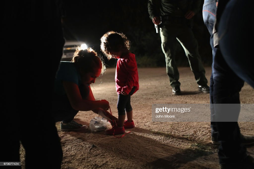 A Honduran mother removes her two-year-old daughter's shoe laces, as required by U.S. Border Patrol agents, after being detained near the U.S.-Mexico border on June 12, 2018 in McAllen, Texas. The asylum seekers had rafted across the Rio Grande from Mexico and were detained by federal authorities before being sent to a processing center for possible separation. Customs and Border Protection (CBP) is executing the Trump administration's 'zero tolerance' policy towards undocumented immigrants. U.S. Attorney General Jeff Sessions also said that domestic and gang violence in immigrants' country of origin would no longer qualify them for political asylum status.