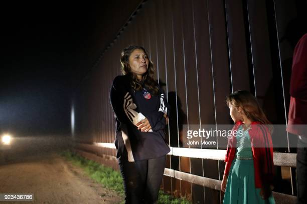 Honduran mother stands with her family at the USMexico border fence on February 22 2018 near Penitas Texas They had turned themselves in to Border...