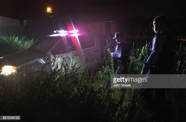 Honduran National Police officers search for a dead body on August 20, 2017 in La Lima, Honduras. Family members had reported that their son had...
