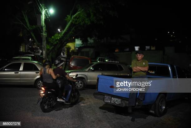 Honduran people are seen on the streets after dark in the Santa Anita neighborhood in Tegucigalpa on December 3 despite the state of emergency and...