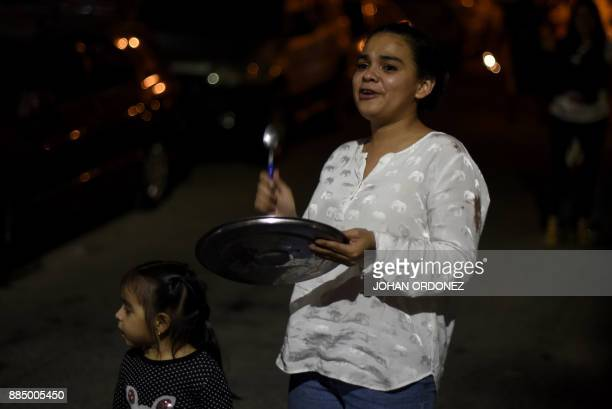 Honduran people chant slogans and bang cooking pots in protest after curfew in Tegucigalpa on December 3 despite the state of emergency and a 10day...