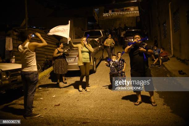 Honduran people chant slogans and bang on cooking pots in protest after curfew in Tegucigalpa on December 3 despite the state of emergency and a...