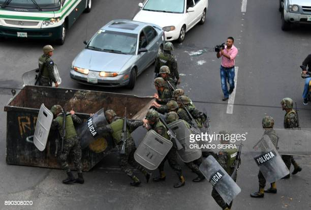 Honduran police members move a skip set by supporters of presidential candidate for Honduras' Opposition Alliance against Dictatorship Salvador...