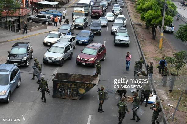 Honduran police members prepare to move a skip set by supporters of presidential candidate for Honduras' Opposition Alliance against Dictatorship...