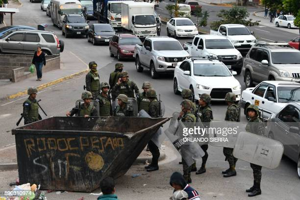 Honduran police members stand after moving a skip which was blocking the street set by supporters of presidential candidate for Honduras' Opposition...
