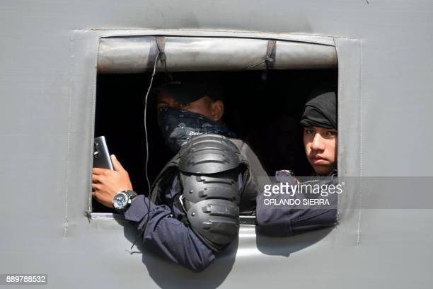 Honduran Police officers in riot gear stand alert as supporters of presidential candidate for Honduras' Opposition Alliance against Dictatorship...