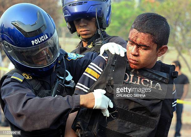 A Honduran policeman takes a police bulletproff vest off from a member of a mara injured during clashes in Tegucigalpa on April 18 2011 At least six...