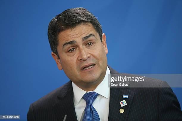 Honduran President Juan Orlando Hernandez speaks to the media with German Chancellor Angela Merkel following talks at the Chancellery on October 27,...