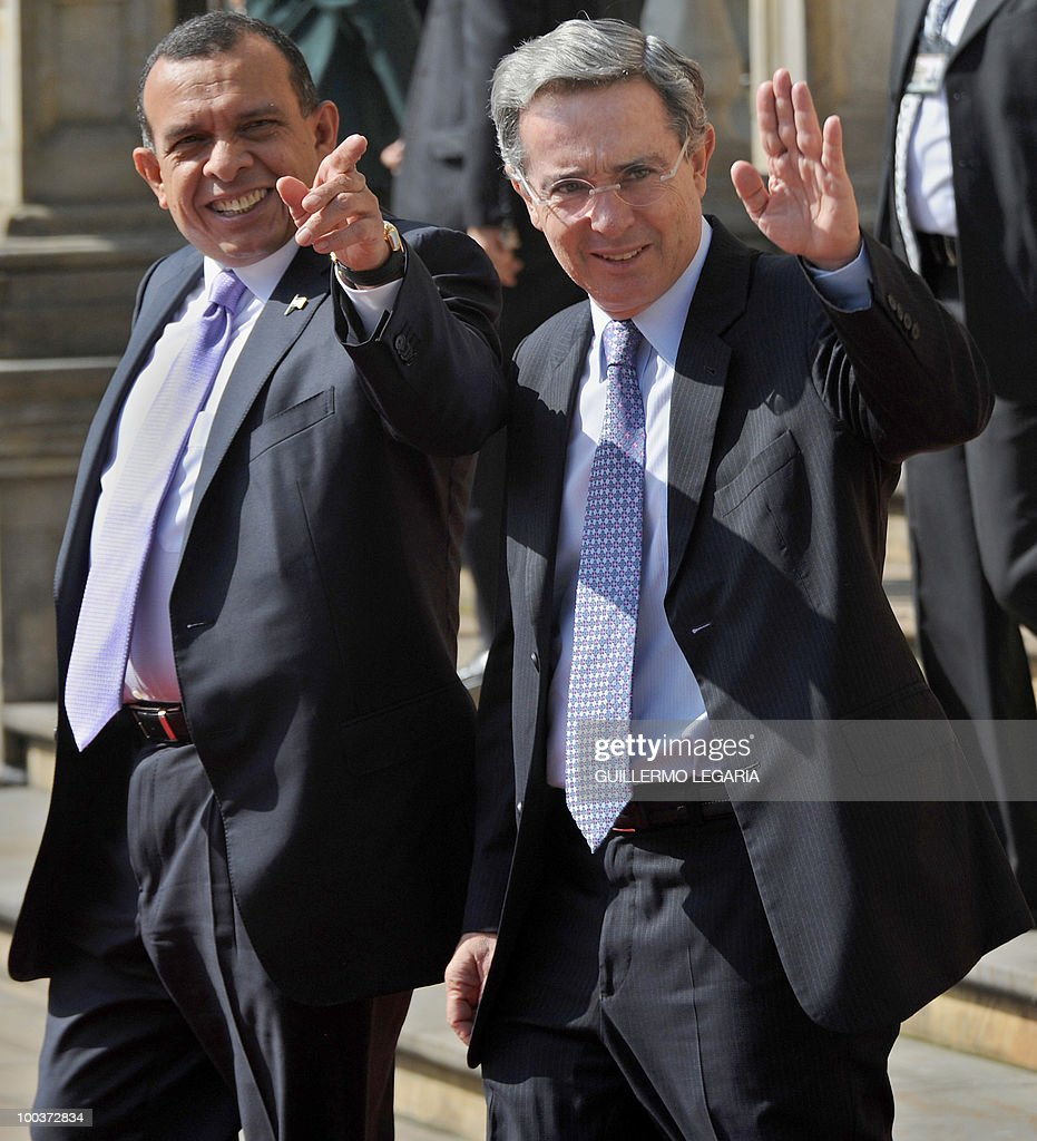 Honduran President Porfirio Lobo (L) and his Colombian counterpart Alvaro Uribe wave during a welcoming ceremony at Narino Palace in Bogota on May 24, 2010. Lobo is on a two-day official visit. AFP PHOTO/Guillermo Legaria