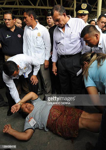 Honduran President Porfirio Lobo stands as his security personnel takes care of a woman relative of one of the prison fire victims who fainted at his...
