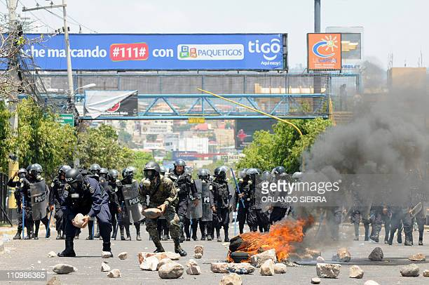 Honduran riot police clear a barricade made out of tires on fire and stones placed on March 28 2011 on an avenue in Tegucigalpa by teachers on strike...