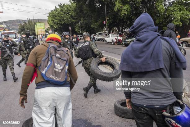 Honduran security forces clear a road which is blocked by supporters of the opposition political party 'Alianza' due to the political turmoil caused...