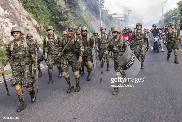Honduran security forces prepare to clear a road which was blocked by supporters of the opposition political party 'Alianza' due to the political...
