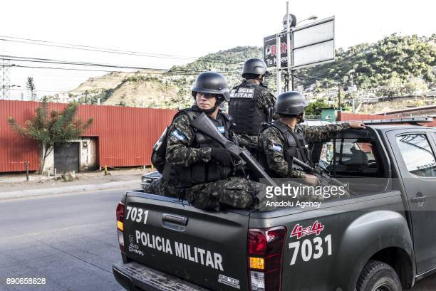 Honduran security forces stand guard during a protest organised by supporters of the opposition political party 'Alianza' due to the political...